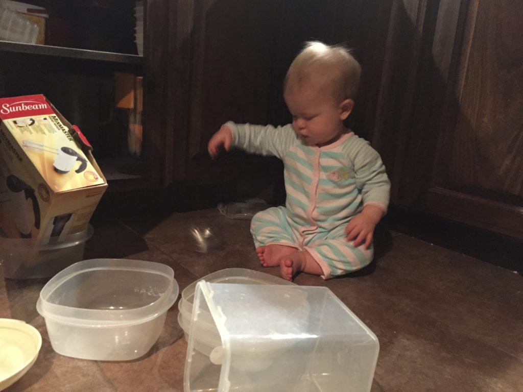 baby playing in tupperware